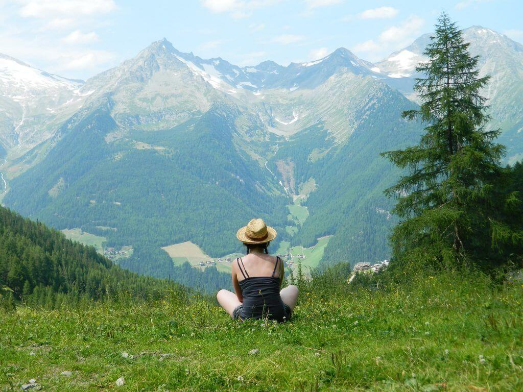 zena v horach sedici na trave
