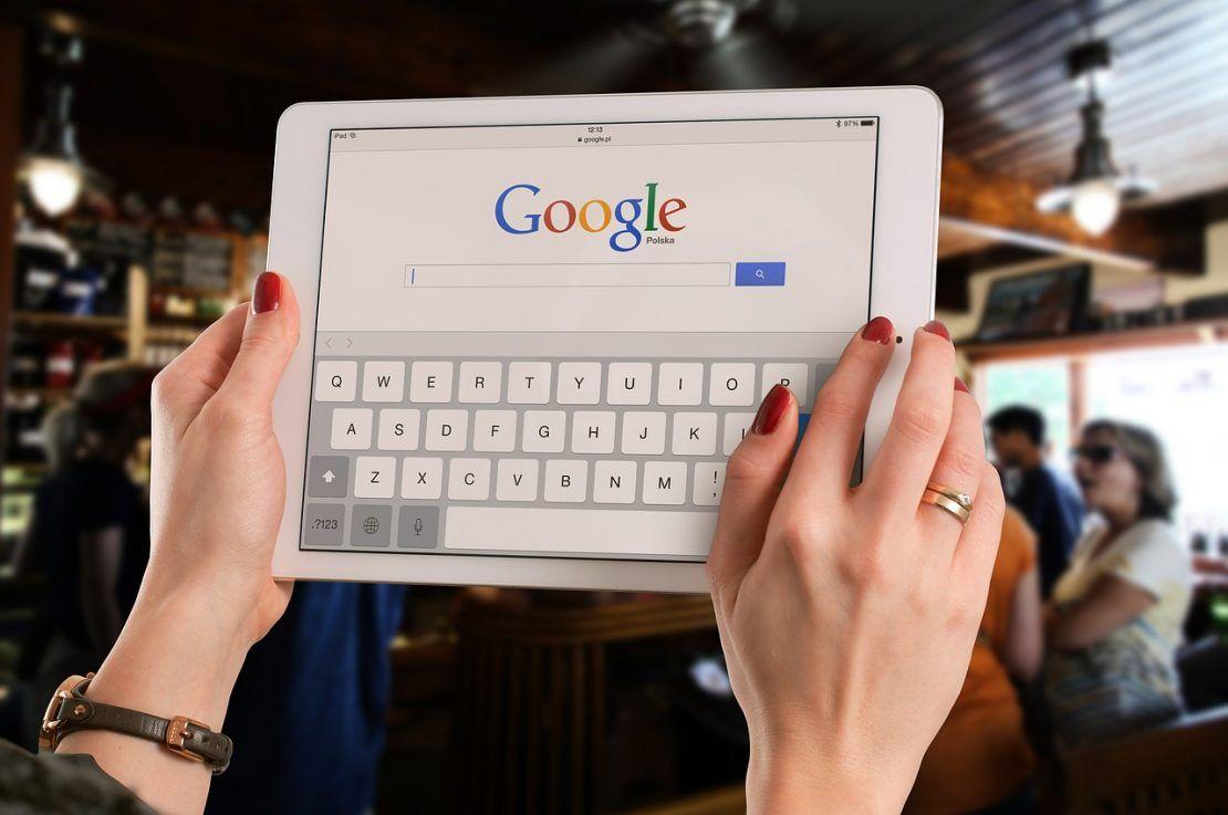ruky drzici tablet, na obrazovce tabletu je prohlizec Google s moznosti hledat