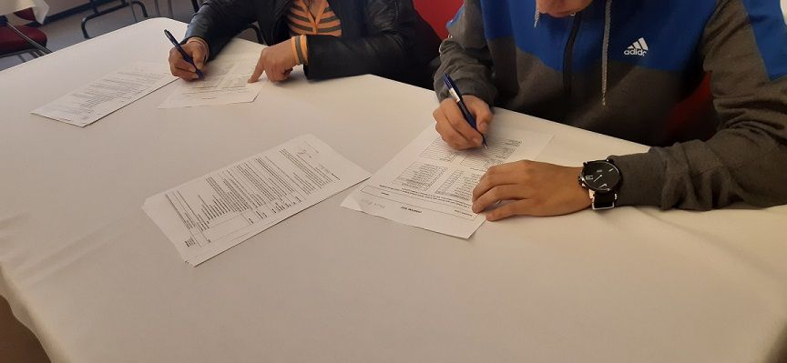 fotografie z testovani, lide vyplnuji testy na papire