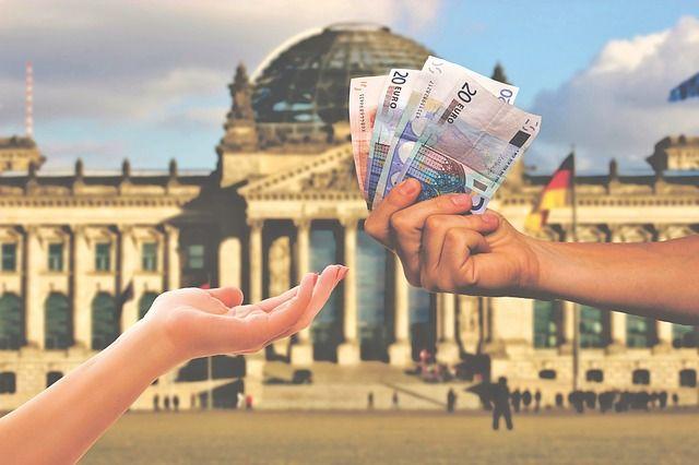 podavani penez z ruky do ruky v pozadi budova nemeckeho parlamentu